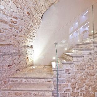 Ejemplo de escalera en L, actual, pequeña, con escalones de piedra caliza, contrahuellas de piedra caliza y barandilla de vidrio