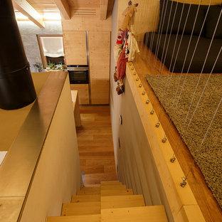Esempio di una piccola scala a rampa dritta rustica con pedata in legno, nessuna alzata e parapetto in cavi
