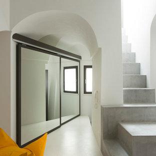 На фото: маленькая прямая лестница в средиземноморском стиле с бетонными ступенями и бетонными подступенками