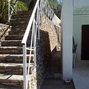 Ispirazione per una scala a rampa dritta mediterranea di medie dimensioni con pedata in pietra calcarea, alzata in pietra calcarea e parapetto in metallo