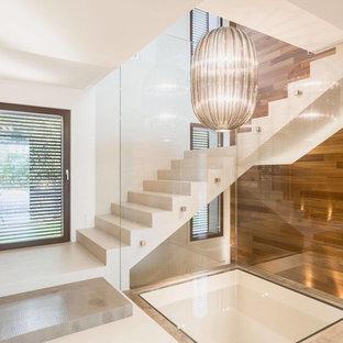 Diseño de escalera en L, contemporánea, grande, con contrahuellas de mármol