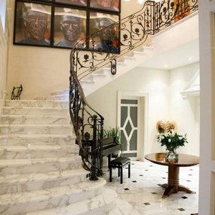 ヴェネツィアの広い大理石のモダンスタイルのおしゃれなサーキュラー階段 (大理石の蹴込み板、金属の手すり) の写真