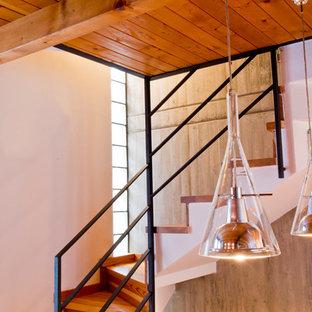 """Immagine di una piccola scala a """"U"""" rustica con pedata in legno, alzata in legno e parapetto in metallo"""