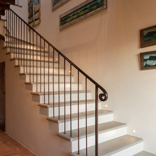 Design ideas for a large rural l-shaped metal railing staircase in Other with limestone treads.