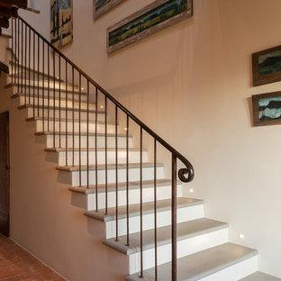Diseño de escalera en L, de estilo de casa de campo, grande, con escalones de piedra caliza y barandilla de metal