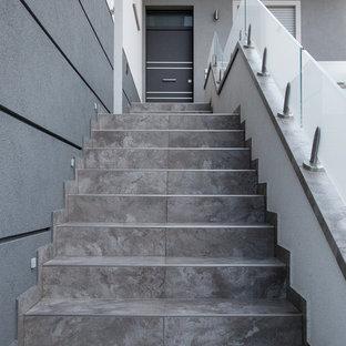 Ejemplo de escalera recta, actual, de tamaño medio, con escalones con baldosas, contrahuellas con baldosas y/o azulejos y barandilla de vidrio