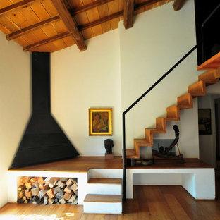 Ispirazione per una scala a rampa dritta minimalista con pedata in legno, alzata in legno e parapetto in metallo