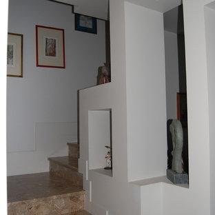 Ejemplo de escalera en L, ecléctica, pequeña, con escalones de mármol y contrahuellas de mármol