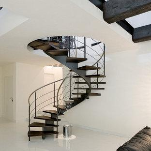 Ispirazione per una scala a chiocciola design con pedata in legno, nessuna alzata e parapetto in metallo