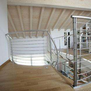 Immagine di una grande scala a chiocciola minimalista con pedata in legno verniciato, nessuna alzata e parapetto in metallo