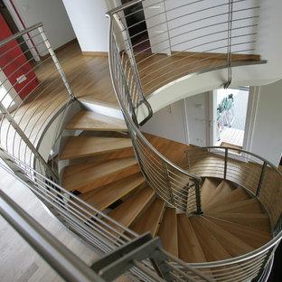 Imagen de escalera de caracol, minimalista, grande, sin contrahuella, con escalones de madera pintada y barandilla de metal