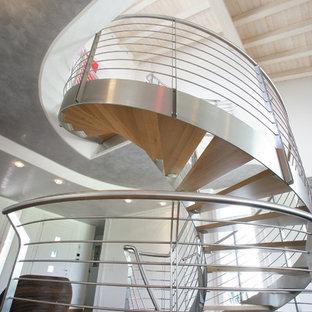Foto di una grande scala a chiocciola moderna con pedata in legno verniciato, nessuna alzata e parapetto in metallo