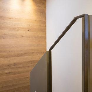 """Ispirazione per una grande scala a """"U"""" minimalista con pedata in ardesia, alzata in ardesia, parapetto in metallo e pareti in legno"""
