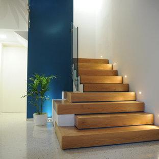 """Esempio di una grande scala a """"L"""" minimal con pedata in legno, alzata in legno e parapetto in vetro"""