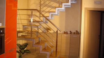 Scala portante in ferro verniciato, gradini in Rovere e ringhiera in acciaio