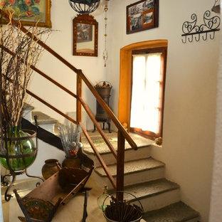 Diseño de escalera en U, rural, grande, con escalones de piedra caliza, contrahuellas de hormigón y barandilla de madera