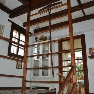 Foto de escalera en U, rural, grande, con escalones de piedra caliza, contrahuellas de hormigón y barandilla de madera
