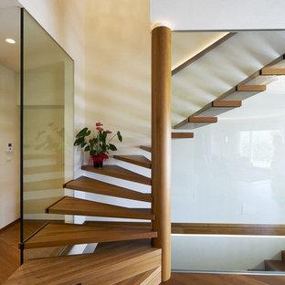 """Foto di una scala a """"L"""" contemporanea con pedata in legno, nessuna alzata e parapetto in materiali misti"""