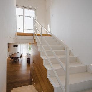 Modelo de escalera boiserie, minimalista, con barandilla de metal y boiserie