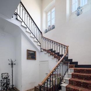 Ejemplo de escalera en U, mediterránea, con escalones enmoquetados, contrahuellas enmoquetadas y barandilla de varios materiales
