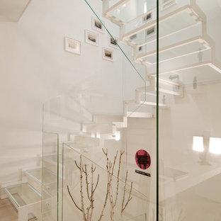 Modern inredning av en u-trappa i glas, med räcke i glas och öppna sättsteg