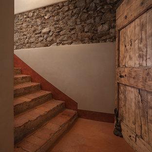 Ejemplo de escalera en U, campestre, grande, con escalones de terracota y contrahuellas de terracota