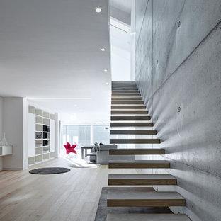 Foto di una grande scala sospesa minimalista con pedata in legno e nessuna alzata
