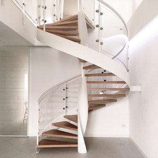 Immagine di una grande scala a chiocciola moderna con pedata in legno