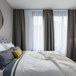 Mittelgroßes Modernes Hauptschlafzimmer ohne Kamin mit weißer Wandfarbe, braunem Holzboden und braunem Boden in Berlin