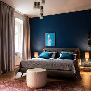 Immagine di una camera da letto eclettica di medie dimensioni con pareti blu, pavimento in legno verniciato e pavimento marrone