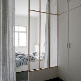 Modelo de dormitorio principal, minimalista, de tamaño medio, con paredes blancas, suelo de madera oscura, estufa de leña, marco de chimenea de baldosas y/o azulejos y suelo negro