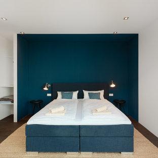 Mittelgroßes Modernes Gästezimmer ohne Kamin mit blauer Wandfarbe, dunklem Holzboden und braunem Boden in München