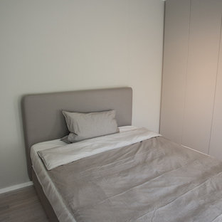 This is an example of a small contemporary loft-style bedroom in Munich with grey walls, light hardwood floors and grey floor.