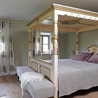 Mittelgroßes Country Hauptschlafzimmer ohne Kamin mit grüner Wandfarbe, braunem Holzboden und braunem Boden