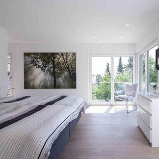 Großes Modernes Hauptschlafzimmer ohne Kamin mit weißer Wandfarbe, hellem Holzboden und braunem Boden in Sonstige