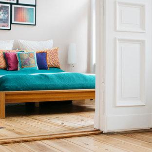 Diseño de dormitorio principal, contemporáneo, de tamaño medio, con paredes blancas, suelo de madera clara, suelo marrón y chimeneas suspendidas