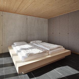 Modelo de dormitorio minimalista con paredes grises y suelo de pizarra