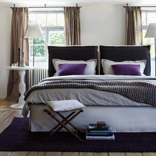 Mittelgroßes Country Schlafzimmer mit weißer Wandfarbe und braunem Holzboden in Hamburg