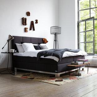 Idées déco pour une chambre d'amis industrielle avec un mur blanc et un sol en bois brun.