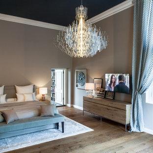 Diseño de dormitorio principal, contemporáneo, extra grande, con paredes beige, suelo de madera en tonos medios, estufa de leña, marco de chimenea de baldosas y/o azulejos y suelo marrón