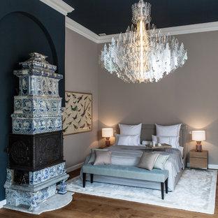 Modelo de dormitorio principal, contemporáneo, extra grande, con paredes beige, suelo de madera en tonos medios, estufa de leña, marco de chimenea de baldosas y/o azulejos y suelo marrón