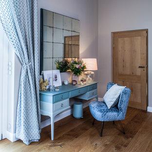 ハンブルクのコンテンポラリースタイルのおしゃれな主寝室 (ベージュの壁、無垢フローリング、薪ストーブ、タイルの暖炉まわり、茶色い床) のレイアウト