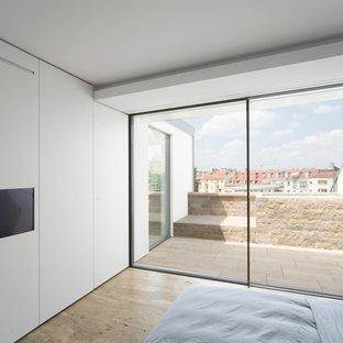 На фото: хозяйская спальня в современном стиле с белыми стенами и полом из травертина без камина с