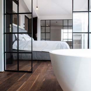 Design ideas for a large industrial master bedroom in Berlin with white walls, medium hardwood floors, no fireplace and brown floor.