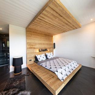 Esempio di un'ampia camera da letto stile loft shabby-chic style con pareti bianche, pavimento in cemento e pavimento nero