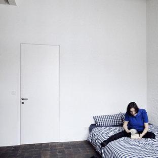 Diseño de dormitorio urbano con paredes blancas, suelo de ladrillo y suelo rojo