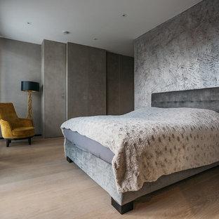 Mittelgroßes Modernes Hauptschlafzimmer ohne Kamin mit grauer Wandfarbe, braunem Holzboden und braunem Boden in Hamburg