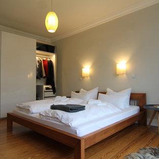 Réalisation d'une chambre parentale design de taille moyenne avec un mur gris, un sol en bois brun, aucune cheminée et un sol marron.