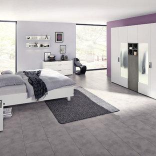 Modelo de dormitorio contemporáneo, grande, sin chimenea, con paredes púrpuras, suelo laminado y suelo gris