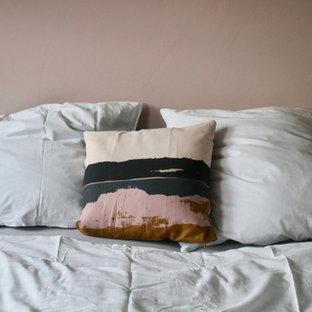 Foto de dormitorio principal, nórdico, de tamaño medio, con paredes rosas, suelo laminado y suelo marrón